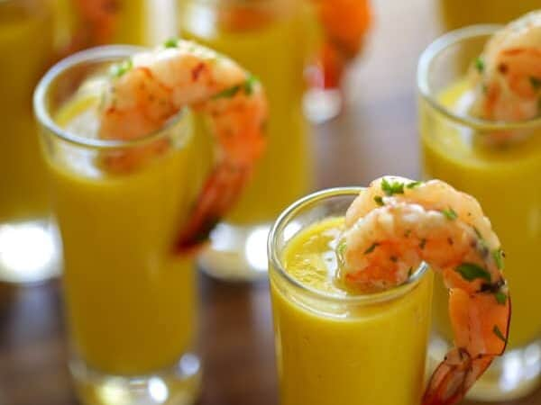 Vertical image of shot glasses filled with gazpacho soup and shrimp tails