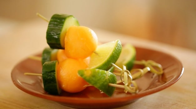 Cucumber and melon garnish on toothpick for Aqua Fresca