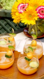 Aqua Fresca in short glass with cantaloupe and cucumber garnish