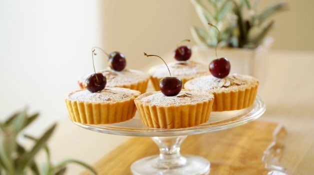 Cherry Bakewell Tart Recipe with cherry on top on cake stand
