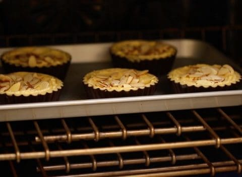 Cherry bakewell tarts in oven