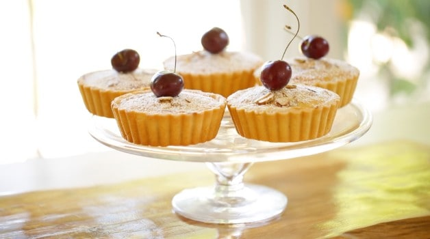 Cherry Bakewell Tart Recipe with cherry on top on cake stand close up