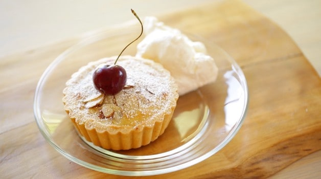 Cherry Bakewell tart with whipped cream on glass plate