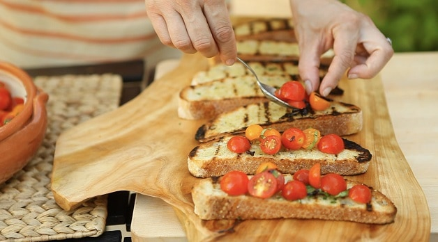 Assembling Bruschetta tomato mixture on grilled bread