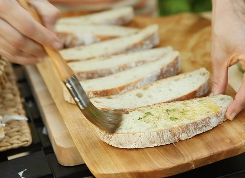 Brushing sliced ciabatta with garlic oil mixture