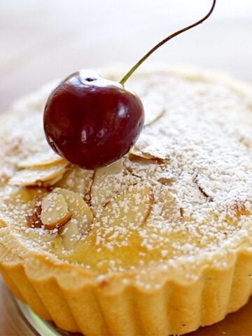 Cherry Bakewell Tart on a plate with cherry garnish