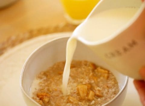 Adding milk to bowl of oatmeal
