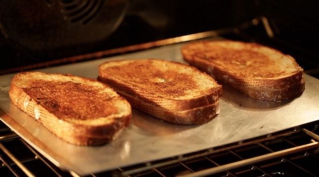 placing grilled cheese sandwiches on a baking tray into the oven