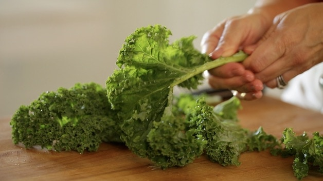 stripping kale leaves from its stalks