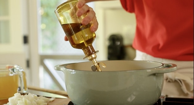 adding olive oil to a dutch oven