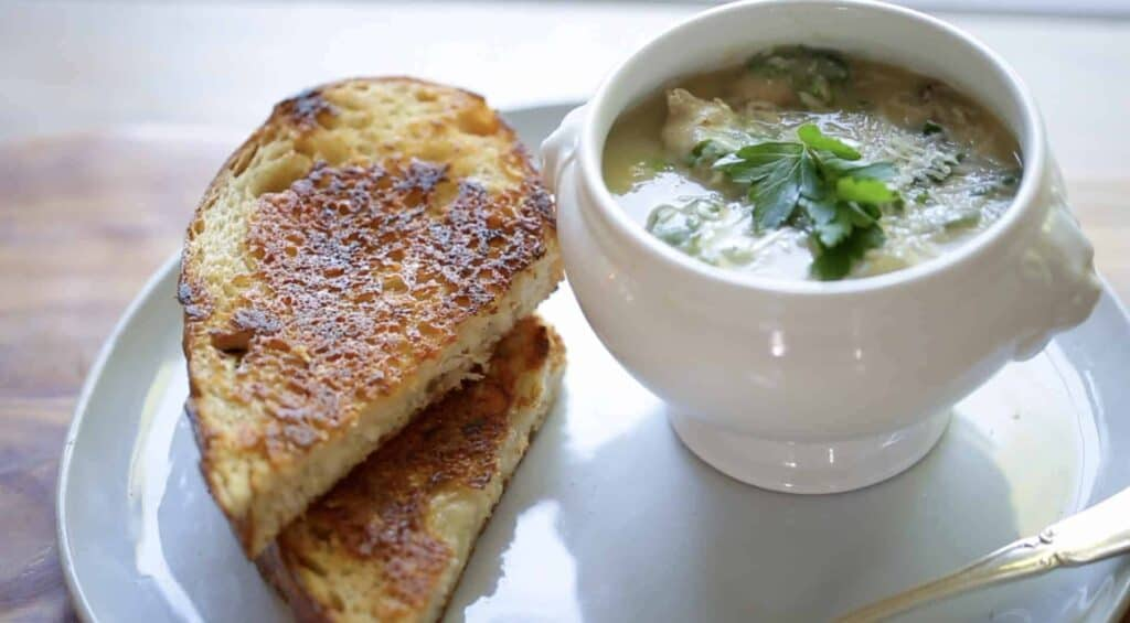 white bean soup in a bowl with grilled cheese sandwiches