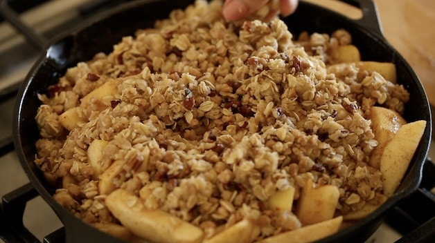topping apples in a skillet with crisp topping