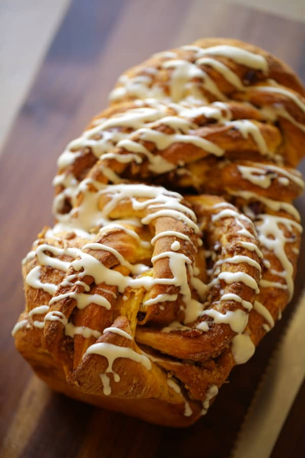 vertical image of a pumpkin cinnamon roll loaf on a cutting board