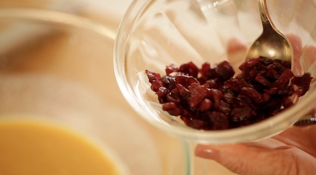adding dried cranberries to bowl
