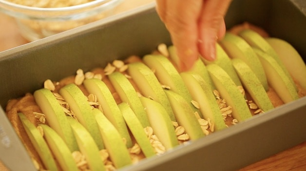 Placing oats on top of cake in loaf pan topped with pears ready for the oven