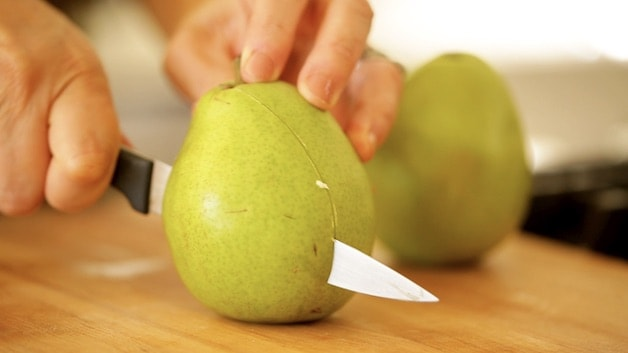 slicing pear in half on a cutting board