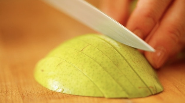 slicing pears on a cutting board into thin slices