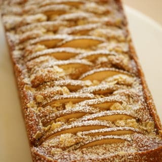 Spiced Pear Cake on a Cake Stand dusted with powdered sugar