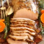 A vertical Image of a Pork loin roast recipe carved on a platter with oranges and rosemary