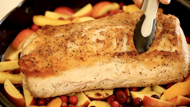 placing pork loin roast on a bed of fruit