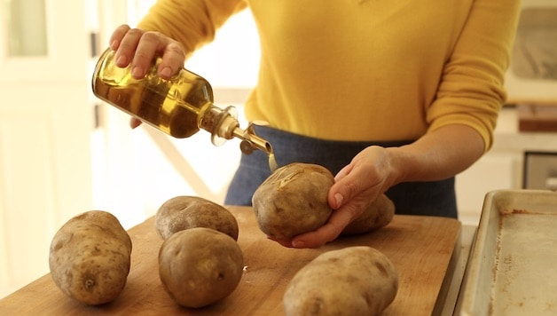 Pouring olive oil on russet potatoes