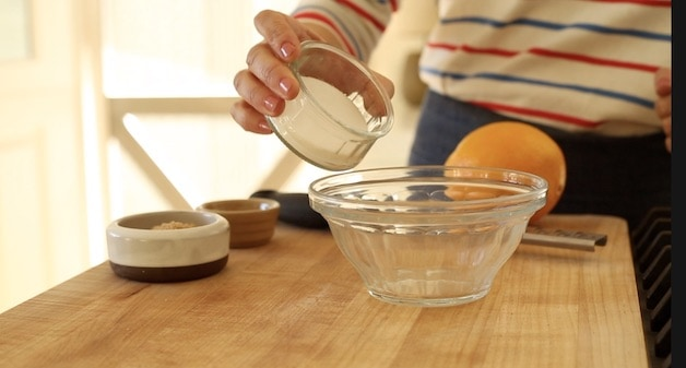 adding white sugar to a glass bowl