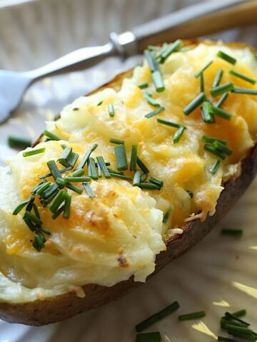 Twice Baked Potato on a white plate garnished with Cheese and Chives