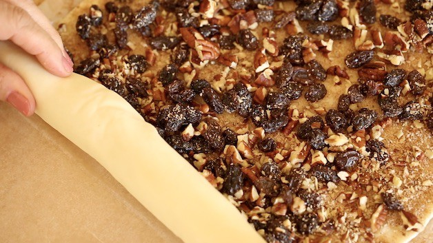 rolling puff pastry sheet filled with pecans and raisins