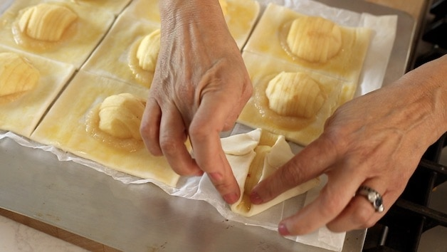 Folding up corners on puff pastry apple squares