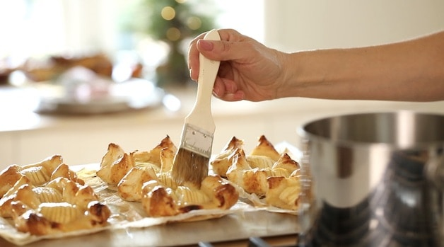 Brushing Apple Jellp on freshly baked apple pastries