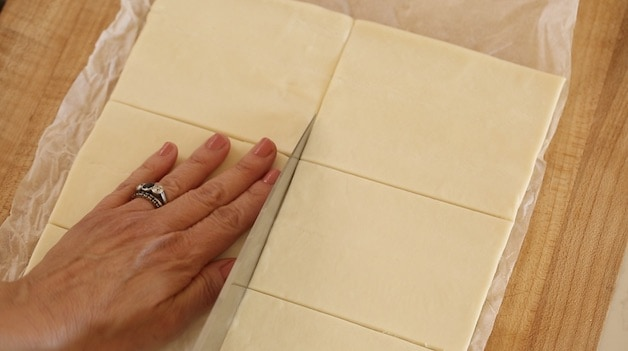 slicing puff pastry dough into rectangles