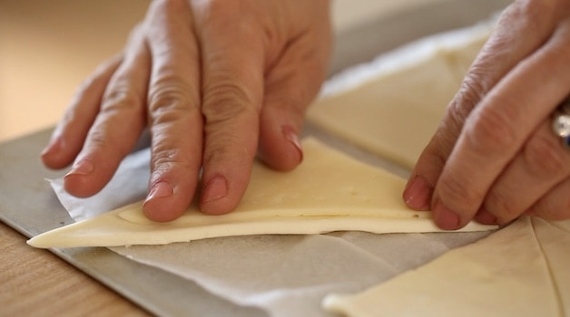 placing cheese on a triangle of puff pastry