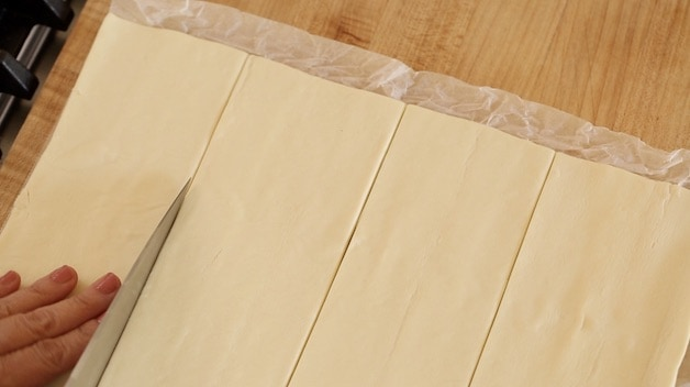 slicing a puff pastry sheet into 4 strips