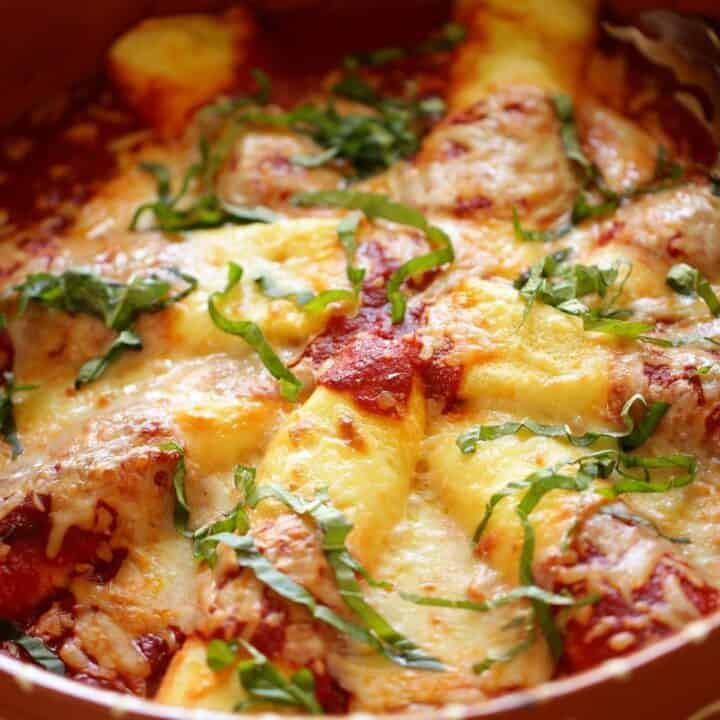 Cheese Manicotti in a terra cotta serving dish with fresh basil