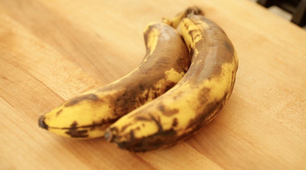 Two rip bananas on a cutting board