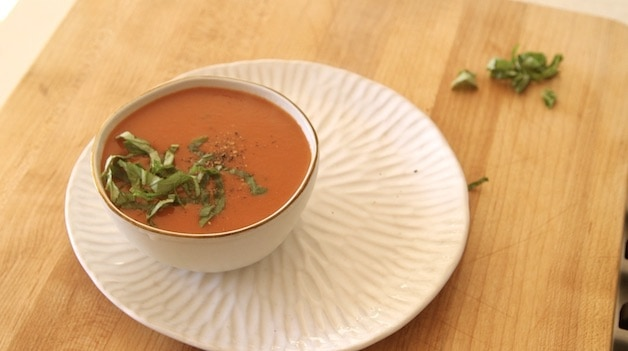 Tomato Soup in Bowl resting on a plate topped with Fresh Basil