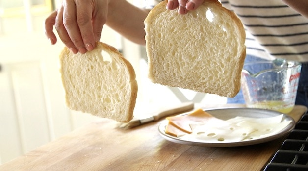 A person holding up 2 slices of White Sandwich Bread