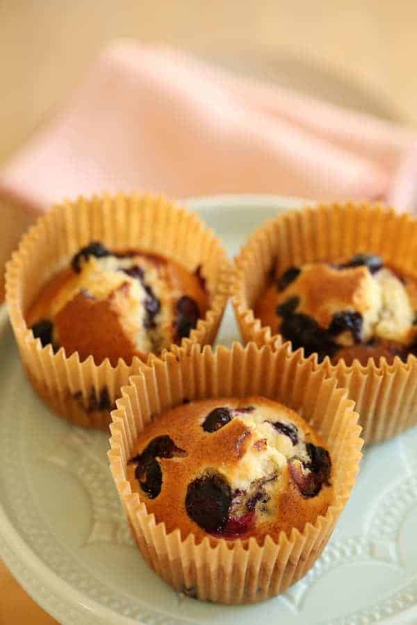 Three blueberry muffins made in the air fryer resting on a cake stand in parchment paper liners