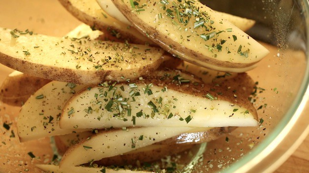 Potato Wedges in bowl with seasoning and rosemary