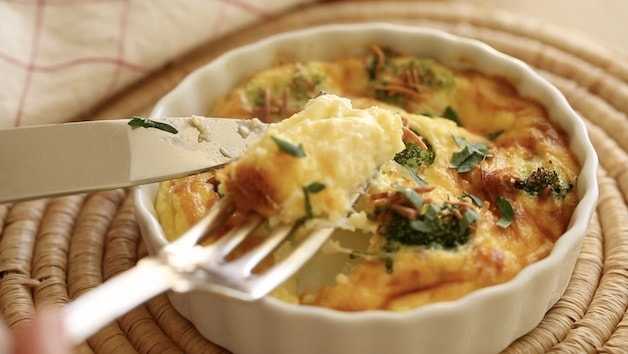 broccoli and cheddar quiche on fork taking a bite