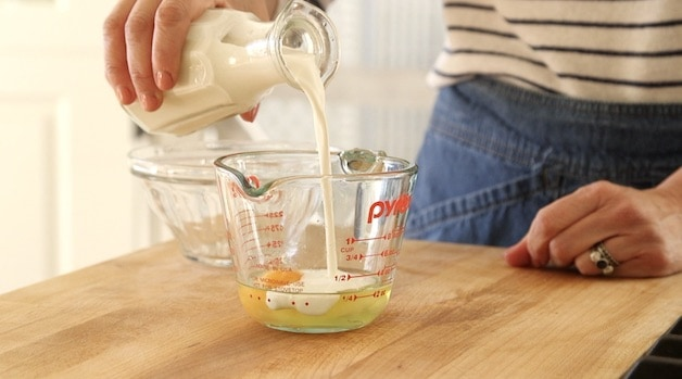 adding heading cream to a pyrex pitcher with egg