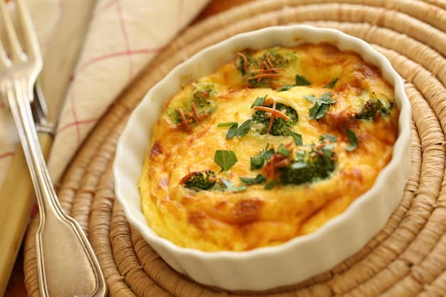 Air Fryer Quiche in a mini white quiche dish on a placemat with fork