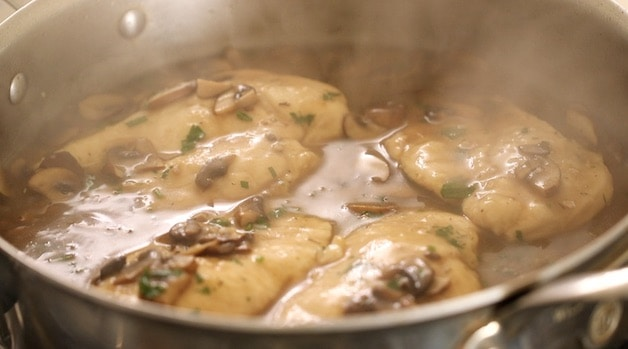 Chicken simmering in sauce in a skillet