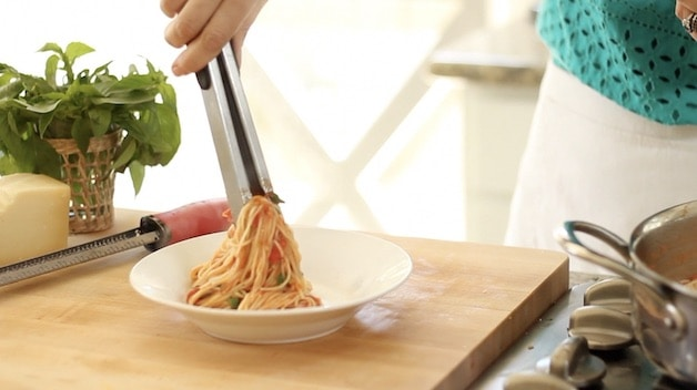 Placing pasta with fresh tomato sauce in a white bowl