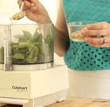 Adding Pinenuts to basil in a food processor