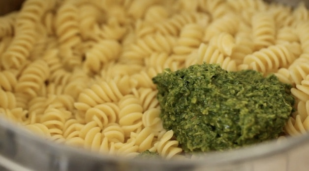 Adding Pesto to a pot of cooked pasta