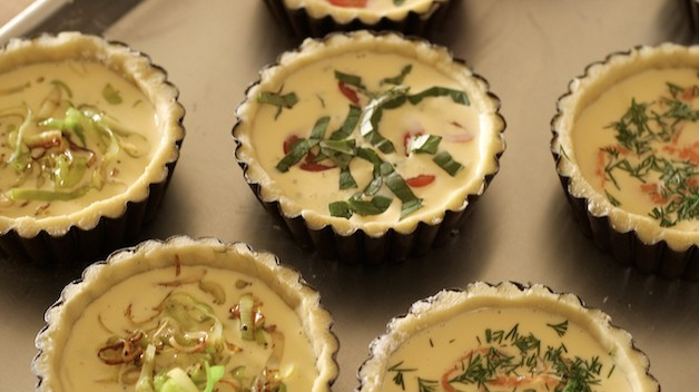 Quiche in tins with different toppings ready for oven