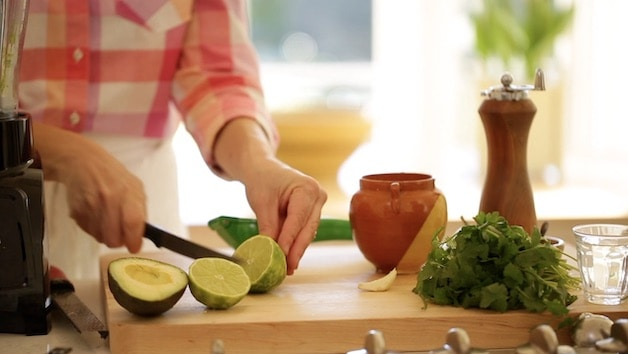 slicing a lime in half on a cutting board