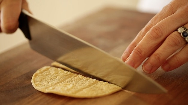 Slicing corn tortillas on a wooden cutting board