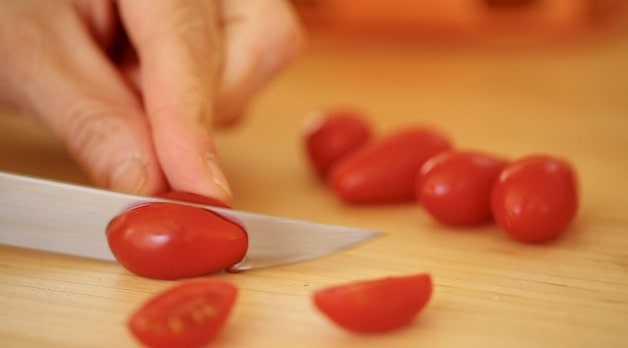 A close up of slicing a tomato on a cutting board